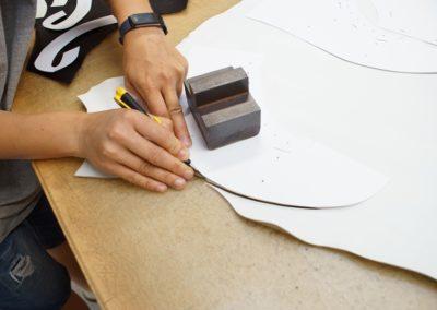 Die einzelnen Musterteile werden am Leder aufgelegt und per Hand ausgeschnitten